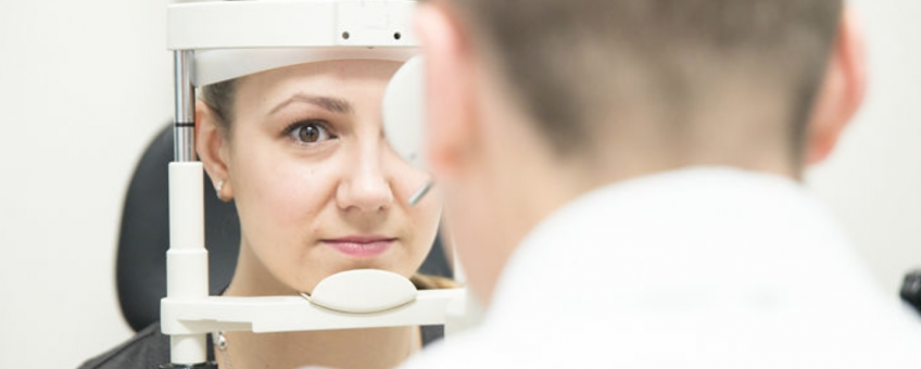 Woman getting eye exam with doctor